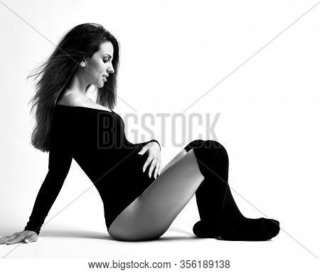 Pregnant Woman In Black Leotard And Stockings. She Is Looking At Her Tummy And Smiling, Sitting On T