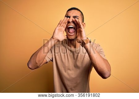 Young handsome african american man wearing casual t-shirt standing over yellow background Shouting angry out loud with hands over mouth