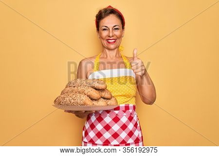 Middle age senior housewife pin up woman wearing 50s style retro dress cooking wholemeal bread happy with big smile doing ok sign, thumb up with fingers, excellent sign