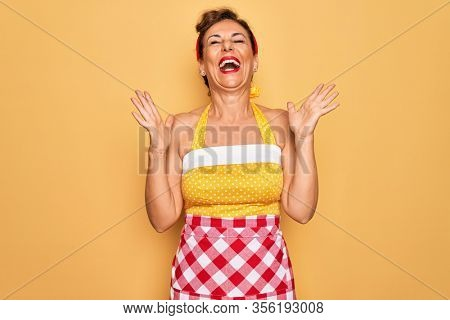 Middle age senior pin up housewife woman wearing 50s style retro dress and apron celebrating mad and crazy for success with arms raised and closed eyes screaming excited. Winner concept