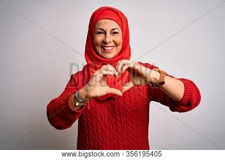 Middle age brunette woman wearing muslim traditional hijab over isolated white background smiling in love doing heart symbol shape with hands. Romantic concept.