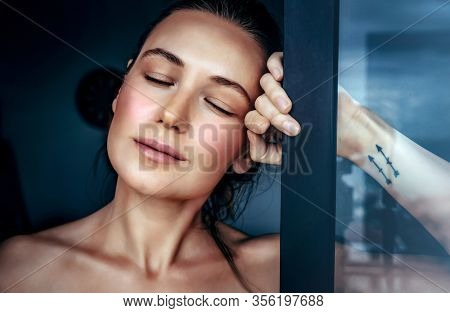 Portrait of a beautiful woman in a dreamy mood with closed eyes standing near the window at home, genuine beauty of a young female