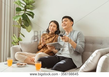 Couple Watching Tv Sitting On A Sofa In The Living Room At Home. Man Is Zapping And The Woman Is Hol