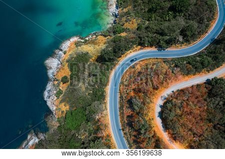 Aerial top down view of the asphalt road on the tropical coastline on Phuket island in Thailand