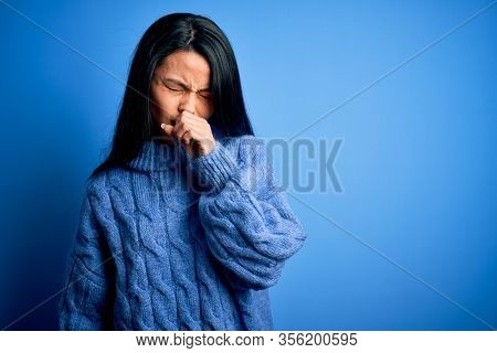 Young beautiful chinese woman wearing casual sweater over isolated blue background feeling unwell and coughing as symptom for cold or bronchitis. Health care concept.