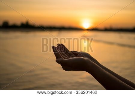 Woman Hands Place Together Like Praying In Front Of Nature Blur Beach Sunset Sky Background.