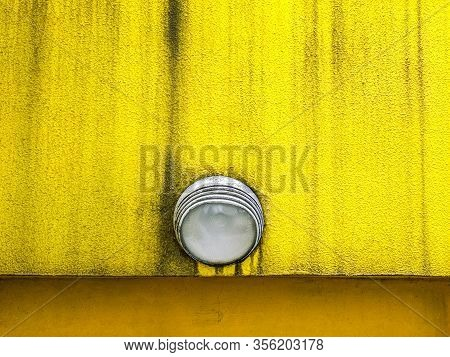 Lighting Fixture On Weathered Textured Plaster Wall Painted Yellow