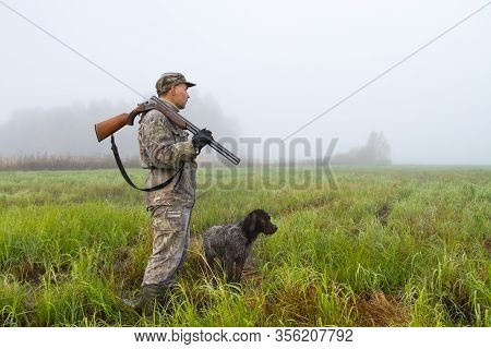 A Hunter With A Shotgun On His Shoulder Examines A Wet Meadow On A Foggy Morning At The Beginning Of