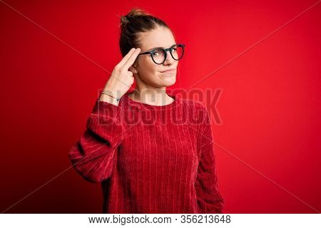 Young beautiful redhead woman wearing casual sweater over isolated red background Shooting and killing oneself pointing hand and fingers to head like gun, suicide gesture.