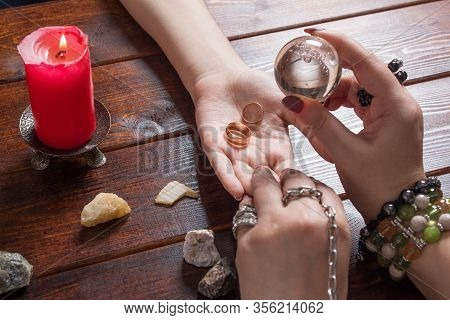 A Fortune Teller Predicts The Fate Of Love With Wedding Rings, A Magic Ball, Lighted Candles And Mag