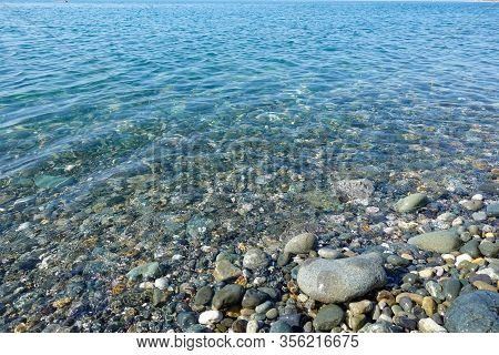 Pebble Beach. Sea View. Sea Shore With Calm Clear Water