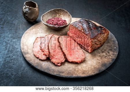 Traditional Commonwealth Sunday roast with sliced cold cuts roast beef with red salt as closeup on a modern design plate with copy space