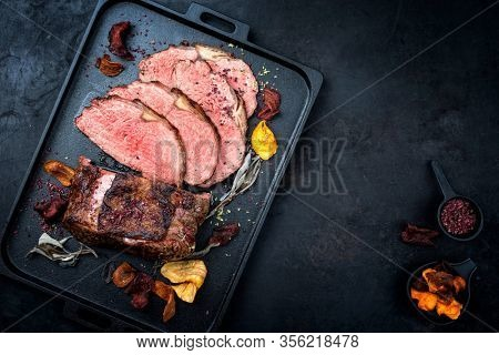 Traditional Commonwealth Sunday roast with sliced cold cuts roast beef with vegetable chips and herbs as top view on a modern design tray with copy space right