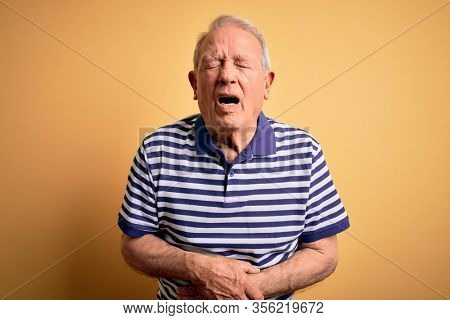Grey haired senior man wearing casual navy striped t-shirt standing over yellow background with hand on stomach because nausea, painful disease feeling unwell. Ache concept.