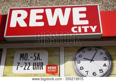 Hannover, Germany - March 17, 2020: Rewe City Logo Sign And Opening Times Or Business Hours At Local