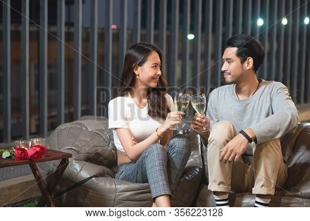 Happy Young Asian Couple Toast Wine Celebrate In Nightclub With Love, Birthday Or Valentine Concept.