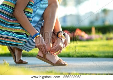 Close Up Of Woman Hands Tying Her Open Summer Sandals Shoes On Sidewalk In Sunny Weather.