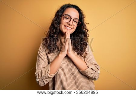 Beautiful woman with curly hair wearing striped shirt and glasses over yellow background praying with hands together asking for forgiveness smiling confident.