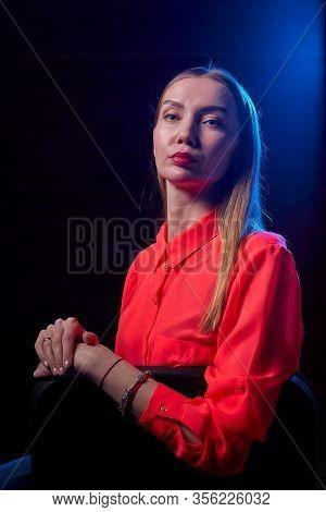 Portrait Of Elegant Woman With Long Hair In Red Dress And Dark Background. Model Posing Doring Studi