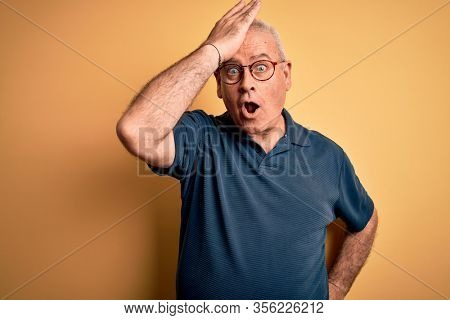 Middle age handsome hoary man wearing casual polo and glasses over yellow background surprised with hand on head for mistake, remember error. Forgot, bad memory concept.
