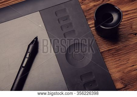 Black Graphic Tablet Lie On A Brown Wooden Background Toning  Photo