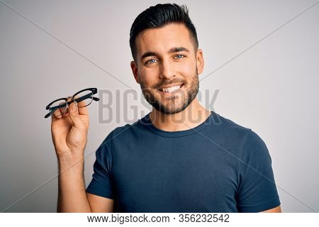 Young handsome man holding correction eye glasses over isolated background with a happy face standing and smiling with a confident smile showing teeth