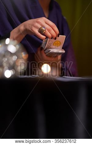 12.02.20. Moscow, Russia. Fortuneteller woman divines on cards at table with candles