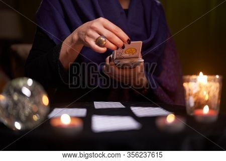 12.02.20. Moscow, Russia. Fortuneteller divines on cards at table with candles in dark room