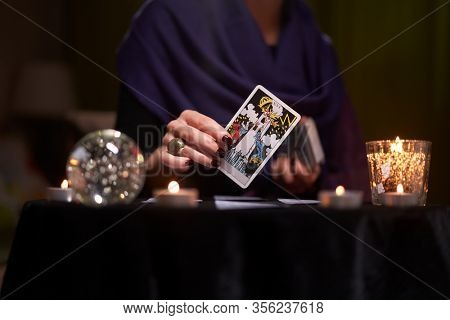 12.02.20. Moscow, Russia. Fortuneteller woman divines on cards at table with candles in dark room