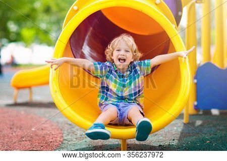 Child Playing On Outdoor Playground. Kids Play On School Or Kindergarten Yard