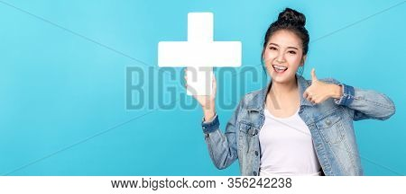 Banner Of Asian Woman Smiling, Showing Plus Or Add Sign And Thumb Up On Blue Background. Cute Asia G