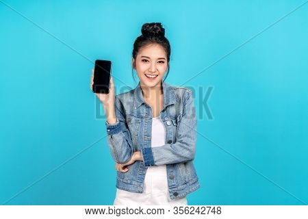 Happy Asian Woman Feeling Happiness And Standing Hold Smartphone On Blue Background. Cute Asia Girl
