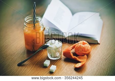 On The Wooden Table There Are Pieces Of Sugar In A Cup, A Tangerine In The Skin, A Glass Mug With Se