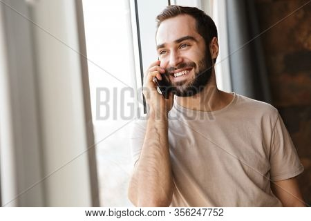 Handsome smiling young bearded man standing at the window at home, looking away, talking on mobile phone