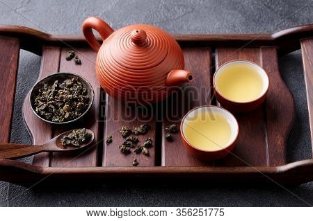Green Tea Oolong In Teapot And Chawan Bowls, Cups On A Wooden Tray. Grey Background. Close Up.