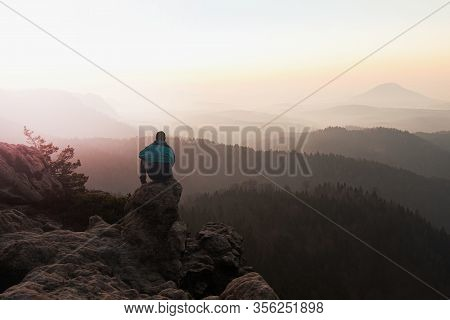 Lost Man Is Sitting On Mountain Peak Watching Sunrise Over A Sea Of Fog