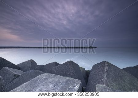 Large Blocks Of Grey Stone With A Lighthouse In The Distance, At Dusk, Scheveningen, The Netherlands