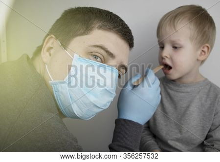 An Otolaryngologist Examines A Child's Throat With A Wooden Spatula. A Possible Diagnosis Is Inflamm