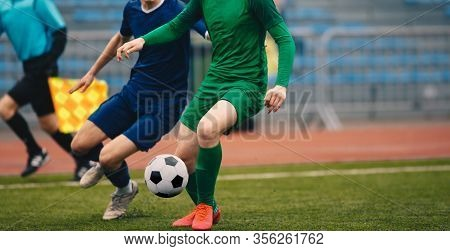 Soccer Football Players Competing For Ball And Kick Ball During Match In The Stadium. Footballers In