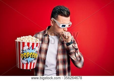 Young handsome caucasian man wearing 3d movie glasses and eating popcorn feeling unwell and coughing as symptom for cold or bronchitis. Health care concept.