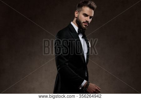 Bothered fashion groom frowning and looking forward while wearing suit, walking on a wallpaper studio background