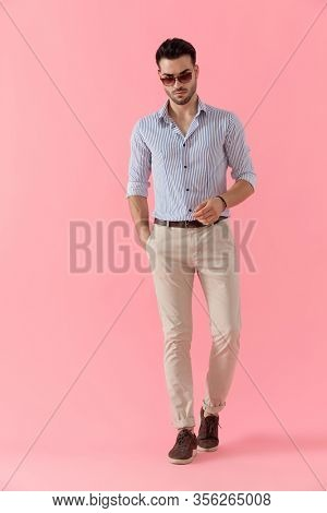 Bothered smart casual man looking forward and frowning with hand in pocket while wearing shirt and sunglasses, walking on pink studio background