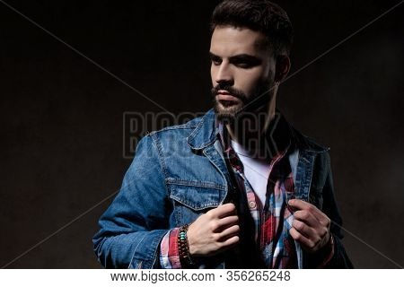 Tough model looking away and adjusting his jacket, standing on wallpaper studio background