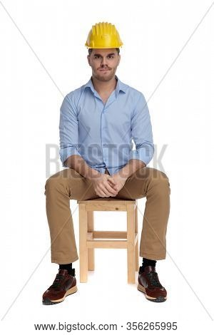 Bothered casual man frowning and wearing hard hat while sitting on a chair on white studio background