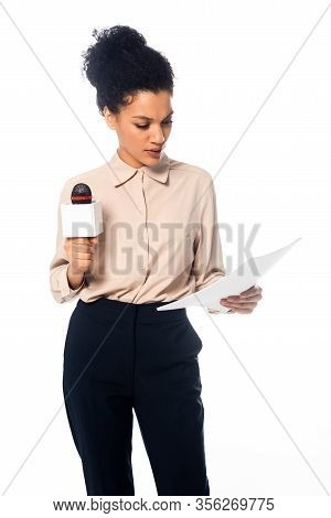 Front View Of Concentrated African American Journalist With Microphone Reading Documents Isolated On