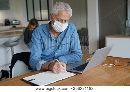 Senior man teleworking, stopping virus spreading