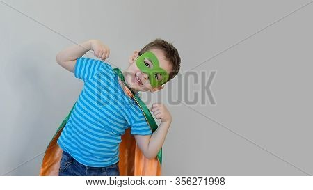 Little Boy Playing A Superhero. Kid In An Superheros Costume. Happy Child. Green Mask, Nature Care C