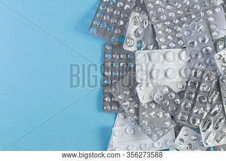 A Pile Used Blister Packs Of Pills On Blue Background. Medical Blisters Packs Opened And Empty Witho