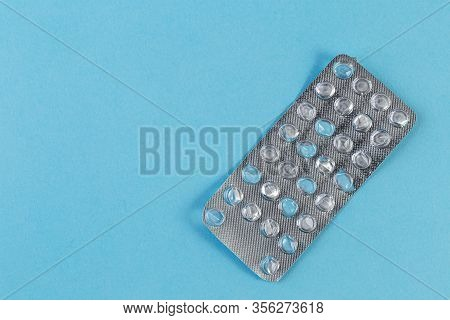 Used Blister Pack From Tablets Medicine On Blue Background. Medical Blister Pack Opened And Empty Wi