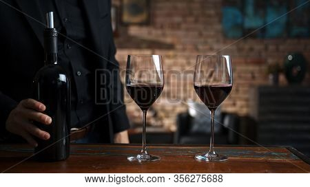 Elegant man tasting and serving red wine in a couple of wine glasses at home in a cosy dark room.